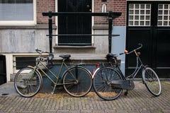 Dos bicicletas en el magro de Amsterdam contra espaldas encorvadas Fotografía de archivo libre de regalías
