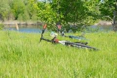 Dos bicicletas y una mochila están en la hierba Imagenes de archivo