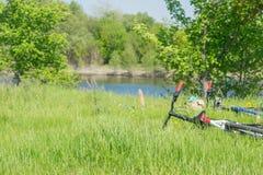 Dos bicicletas y una mochila están en la hierba Fotografía de archivo libre de regalías