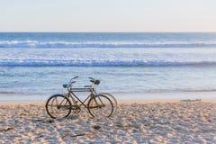 Dos bicis en la playa contra olas oceánicas fotos de archivo libres de regalías