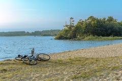 Dos bicis en la playa La línea de la playa arenosa del lago fotografía de archivo