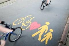 Dos bicis que pasan por el peatón/la bicicleta firman fotos de archivo libres de regalías