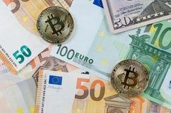 Dos bitcoins de oro en billetes de banco euro Imágenes de archivo libres de regalías