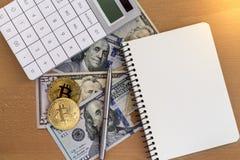 Dos bitcoins, diarios, plumas, y calculadoras de oro en dólar fotografía de archivo libre de regalías