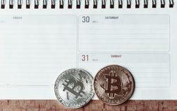 Dos bitcoins son mentira en el cepillado En el calendario son los días pasados de diciembre de 2017 El concepto de monedas crypto Imagen de archivo libre de regalías