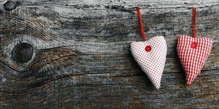 Dos blancos y corazones materiales rojos en un fondo de madera oscuro Foto de archivo