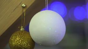 Dos blancos y los juguetes de oro del árbol de navidad cuelgan en un cierre del haz de madera para arriba Fondo borroso la c?mara almacen de video