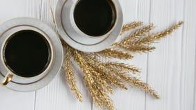 Dos blancos y tazas de café de oro con las ramas de oro decorativas en el fondo de madera blanco Fotografía de archivo