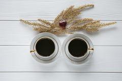Dos blancos y tazas de café de oro con las ramas de oro decorativas y el pequeño corazón del vidrio y rojo en el fondo de madera  Foto de archivo