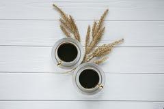 Dos blancos y tazas de café de oro con las ramas de oro decorativas y el pequeño vidrio en el fondo de madera blanco Foto de archivo libre de regalías