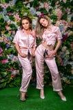 Dos blondes hermosos felices en pijamas y talones rayados atractivos en un fondo de la flor Se colocan cerca juntos y pareciendo  fotografía de archivo libre de regalías