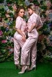 Dos blondes hermosos felices en pijamas y talones rayados atractivos en un fondo de la flor Se unen cercanos fotos de archivo