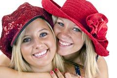 Dos blondes sonrientes en sombreros rojos foto de archivo