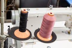 Dos bobinas negras y rosadas grandes con los hilos de acoplamiento grandes montaron en una barra cerca de la máquina de coser en  foto de archivo libre de regalías