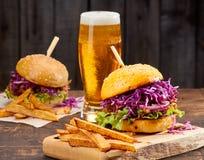 Dos bocadillos con cerdo, las patatas fritas y el vidrio tirados de cerveza en fondo de madera Fotos de archivo