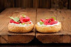 Dos bocadillos con los salmones curados, queso cremoso, perejil, alcaparras Foto de archivo