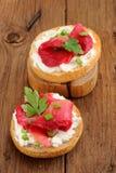 Dos bocadillos con los salmones curados, queso cremoso, perejil, alcaparras Imagen de archivo