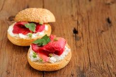 Dos bocadillos con los salmones curados, queso cremoso, perejil, alcaparras Imagen de archivo libre de regalías