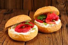 Dos bocadillos con los salmones curados, queso cremoso, perejil, alcaparras Fotos de archivo