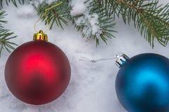 Dos bolas de la Navidad en nieve Imágenes de archivo libres de regalías