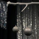 Dos bolas de plata colgantes de la Navidad en fondo oscuro y de plata fotos de archivo