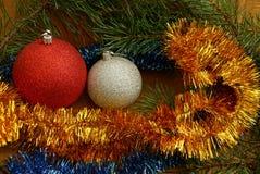 Dos bolas del ` s del Año Nuevo entre los ornamentos y las agujas brillantes Imagen de archivo