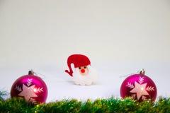 Dos bolas rosadas de la Navidad, juguete rojo Papá Noel del sombrero y decoración de la Navidad en un fondo blanco Foto de archivo libre de regalías