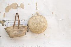 Dos bolsos de la paja que cuelgan en una pared Fotografía de archivo libre de regalías