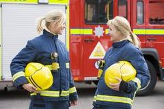 Dos bomberos de sexo femenino por un coche de bomberos Imagen de archivo