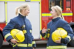 Dos bomberos de sexo femenino por un coche de bomberos Fotografía de archivo