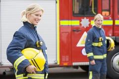 Dos bomberos de sexo femenino por un coche de bomberos Imagenes de archivo