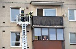 Dos bomberos en la cesta telescópica del auge de coche de bomberos intentan llegar al balcón plano La mujer mayor los está mirand imágenes de archivo libres de regalías