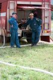 Dos bomberos hacen una pausa el coche de bomberos y miran para arriba fotografía de archivo libre de regalías