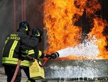 Dos bomberos que apaga el fuego con un fuego ex Imagen de archivo libre de regalías