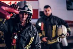 Dos bomberos que llevan un uniforme protector que se coloca al lado de un coche de bomberos Llegada en llamada en la noche imagen de archivo libre de regalías