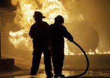 Dos bomberos que se colocan delante de un fuego con la manguera Imagen de archivo
