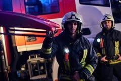Dos bomberos valientes que llevan un uniforme protector que se coloca al lado de un coche de bomberos Llegada en llamada en la no foto de archivo libre de regalías