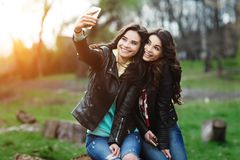 Dos bonitos y mujer joven feliz que usa el teléfono móvil en el parque Los mejores amigos hacen el selfie Foto de archivo