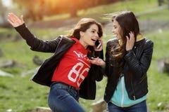 Dos bonitos y mujer joven feliz que usa el teléfono móvil en el parque Mejores amigos Fotos de archivo