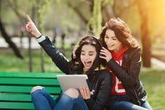Dos bonitos y mujer joven feliz que usa la tableta en el parque Música que escucha de los mejores amigos Imágenes de archivo libres de regalías