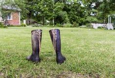 Dos botas de goma en un césped verde cerca de la casa roja en granja Imagen de archivo