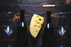 Dos botellas con copas de vino y un pedazo de queso en un fondo de madera imagen de archivo