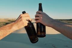 dos botellas de cerveza del hombre que tintinean joven de cerveza en la laguna del desierto fotografía de archivo