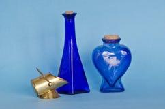 Dos botellas de cristal azules con el objeto de cobre amarillo decorativo foto de archivo libre de regalías