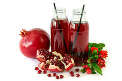 Dos botellas de cristal de jugo de la granada, de fruta, de semillas y de rama floreciente del árbol de granada aislados en blanc Fotos de archivo