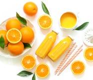 Dos botellas de cristal de zumo, de paja fresca y de naranjas de naranja aislados en la opinión superior del fondo blanco Foto de archivo libre de regalías