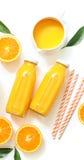 Dos botellas de cristal de zumo, de paja fresca y de naranjas de naranja aislados en la opinión superior del fondo blanco Fotos de archivo