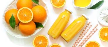 Dos botellas de cristal de zumo, de paja fresca y de naranjas de naranja aislados en la opinión superior del fondo blanco Fotografía de archivo