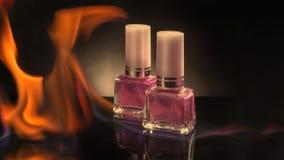 Dos botellas de esmalte de uñas coloreado en un fondo negro que quema en una llama del fuego Foto de archivo
