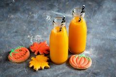 Dos botellas de jugo de la calabaza con la comida horizontal de Halloween de la foto de la paja negra y el concepto de los dulces Foto de archivo